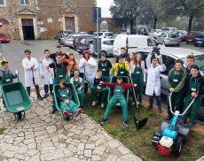 Foto di gruppo dei ragazzi dell'Agrario con tute e nuovi utensili